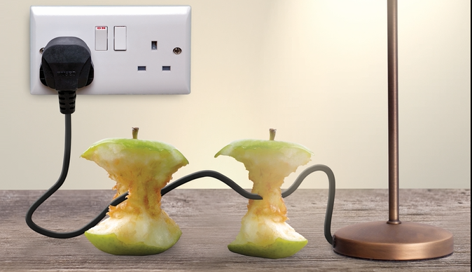 Two apple placed on a wooden side with an eclectic cord running through them to represent natural energy