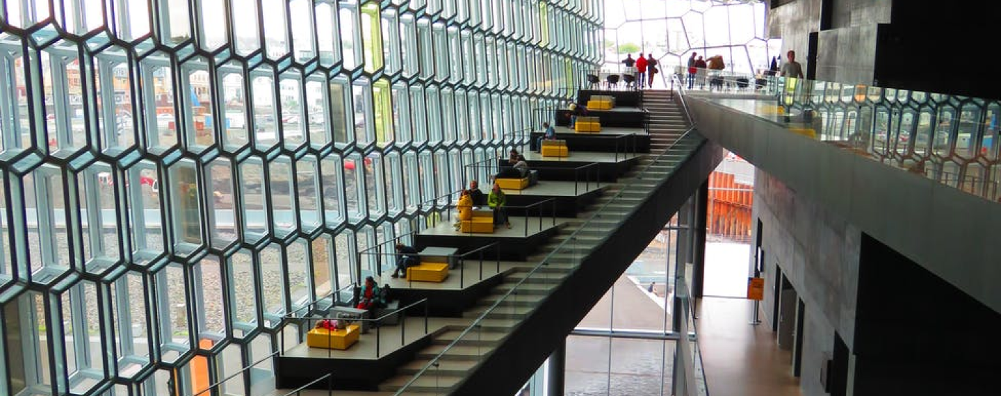 Photo of busy commercial building with stairs running alongside seating area. Walk-way to the right