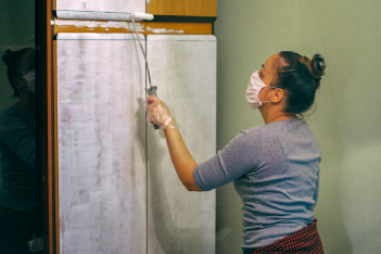 Women wearing a protective mask upcycling a wooden wardrobe by painting it white with a paint roller
