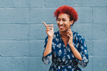Young woman smiling and pointing in front of a blue wall