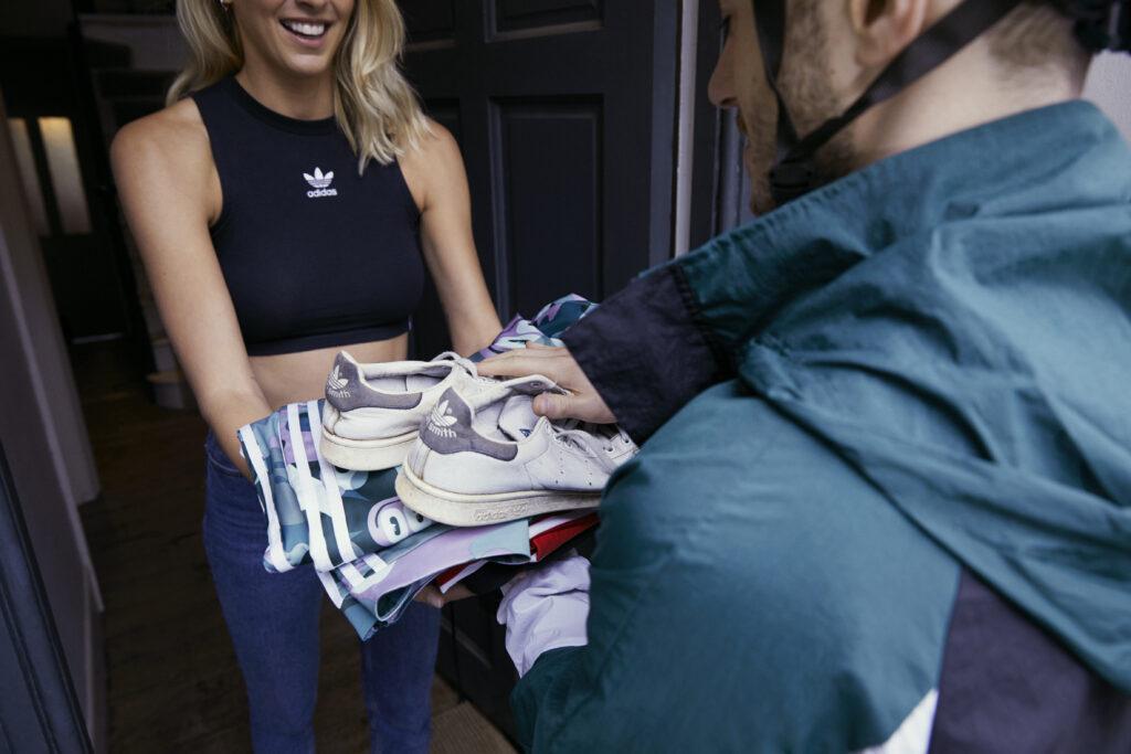 Delivery man giving Zanna Vandijk a parcel of second-hand Adidas clothes