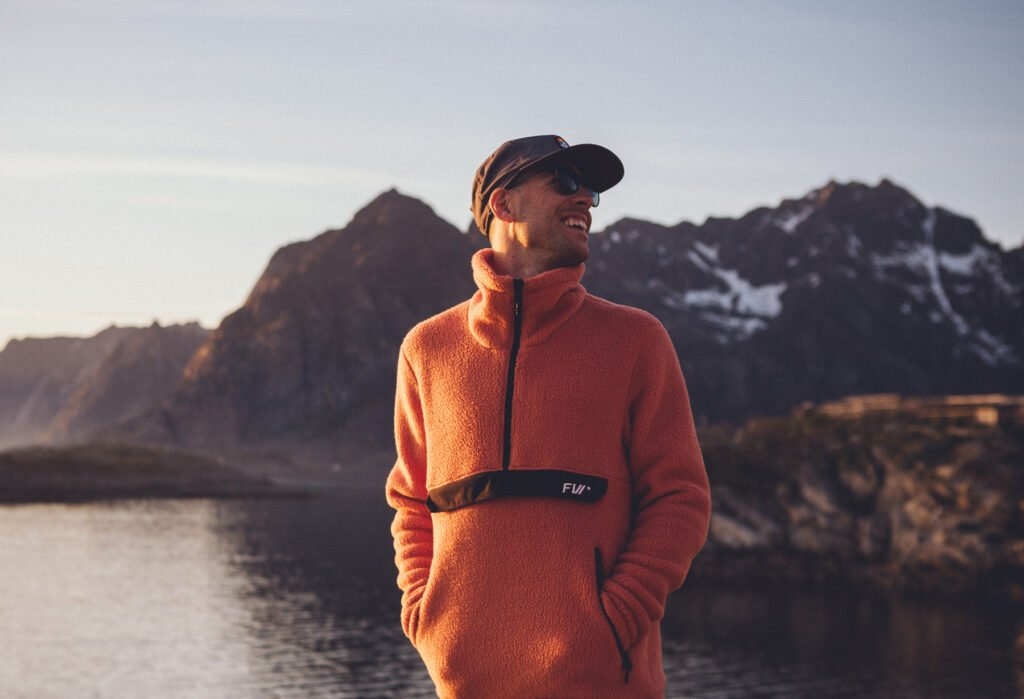 Man in orange fleece smiling in front of mountains