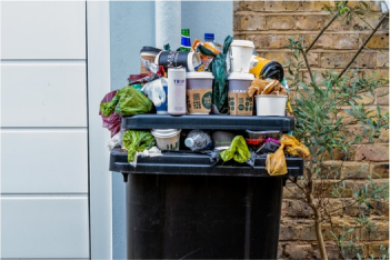 An overflowing black rubbish bin with various packaging placed on top including plastic bags single-use and coffee cups