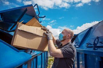 A man wearing a disposable protective mask recycling cardboard boxes at a local environmental recycling centre in the daytime