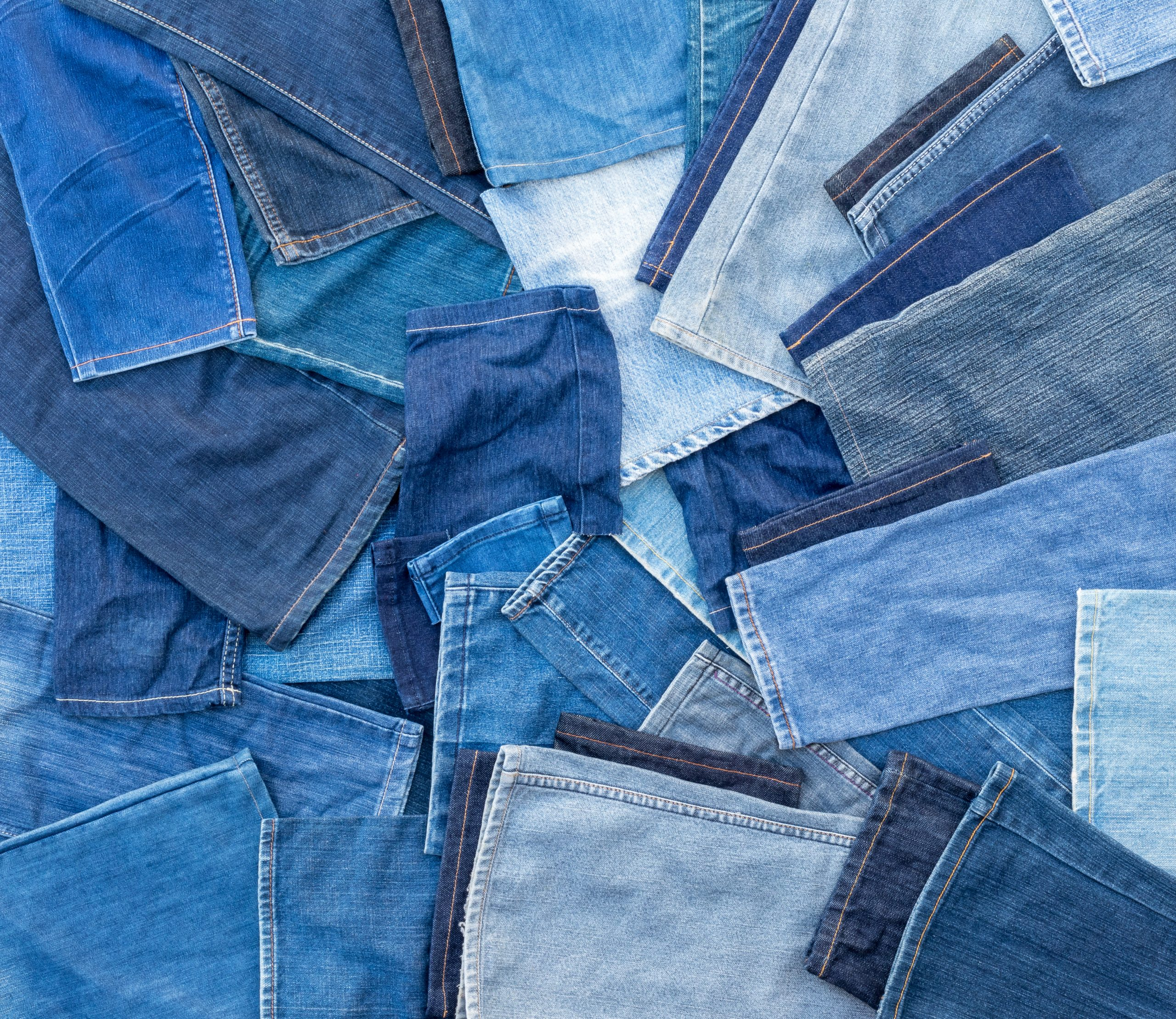 Different shades of blue denim jeans, many of which are left pieces over from sewing repairs.