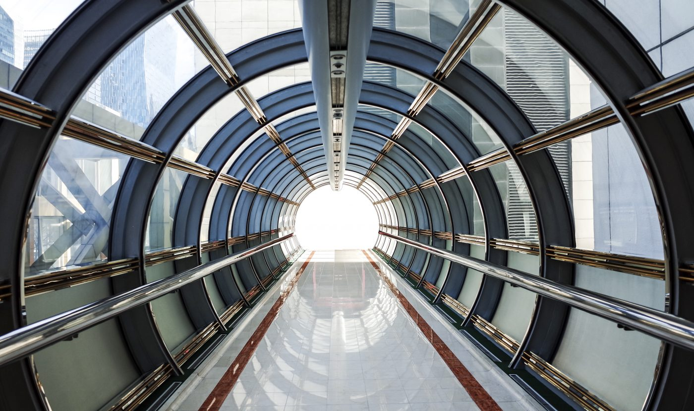 Photograph of a tunnel made from glass and metal leading to a bright light. Tunnel is surrounded by commercial buildings in the city of London
