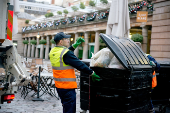 London waste recovery crew emptying large commercial bins