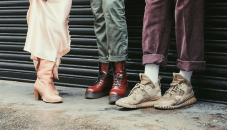 Love Not Landfill charity pop-up shop to show the best second-hand clothes London has to offer. Shot of shoes on 3 models: pink cowboy boots, red Doc Martens and beige Yeezy trainers