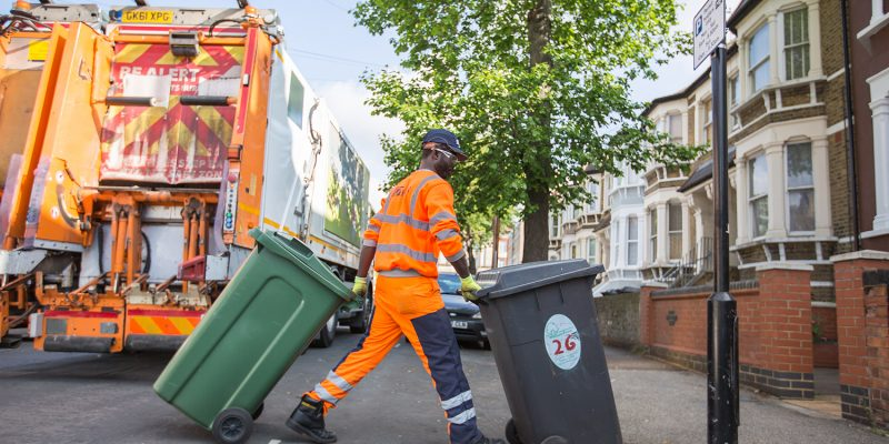 Waste collection crew at work returning two recycling bins after emptying them into the bin truck