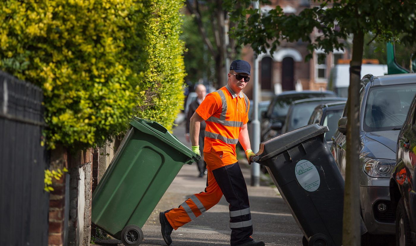 Waste collection employee in sunglasses, looking directly at the camera moving rubbish and recycling bins