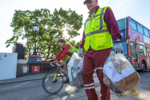 Veolia crew member carrying two clear sacks of commercial recycling waste