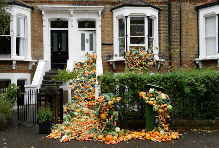 TRiFOCAL food waste campaign: Lots of fruit and vegetables are tumbling down the steps of a Victorian terraced house, out of its windows into the front garden and street, to show how we can reduce food waste to tackle the climate emergency. Photo credit: Jonathan Hordle/PA Wire