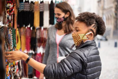 Young woman wearing a protective face mask browsing colourful necklaces outside at a street market stall