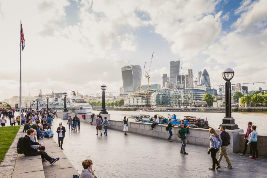 people socialising and walking along the river Thames with a view of the city across the river